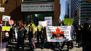 Anti-Islam protesters stand outside Masjid Toronto on Friday, Feb. 17, 2017. (Twitter / @SafiahC)
