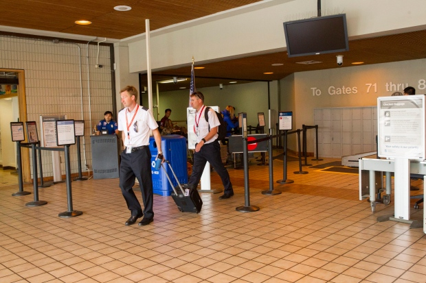 Crew members walk past the TSA area where a man breached security at the Honolulu International Airport Saturday, Feb. 18, 2017, in Honolulu. (Cindy Ellen Russell/The Star-Advertiser via AP)