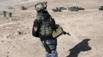 An Iraqi federal police member walks towards the frontline outside the town of Hamam al-Alil, Iraq, Sunday, Feb. 2017. The battle for the western half of Mosul city, which began Sunday, is expected to be prolonged and difficult due to a densely packed civilian population and older, narrower streets.(AP Photo/Bram Janssen)