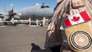 Members of the Canadian Forces work on a CP140 Aurora surveillance plane at the Canadian Forces base Sunday, February 19, 2017 in the Persian Gulf. (Ryan Remiorz/The Canadian Press)