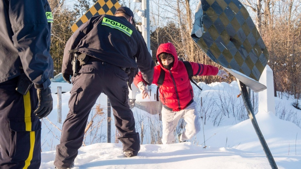 An RCMP officer extends his hand to help a young man from Yemen to cross into Canada at the U.S.-Canada border into Canada near Hemmingford, Que., on Friday, February 17, 2017. (Paul Chiasson/The Canadian Press)