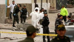 Police and investigators inspect the site where a homemade bomb exploded near the Santamaria bull ring in Bogota, Colombia, Sunday, Feb. 19, 2017. (Ricardo Mazalan/AP Photo)