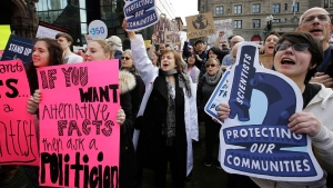 Johanna Klein, of Brookline, Mass., an internal medical doctor, center, holds a placard and chants during a demonstration by members of the scientific community, environmental advocates and supporters, Sunday, Feb. 19, 2017, in Boston.  (AP Photo/Steven Senne)