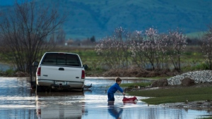 Barr Torrens, 5, plays in flooded neighborhood streets after a deluge of rain and water-runoff flooded much of Maxwell, Calif., Saturday, Feb. 18, 2017. Northwest of Sacramento, several hundred people were evacuated Saturday as overflowing creeks turned the town of Maxwell into a brown pond, with some homes getting 2 feet of water. (Andre Seng/The Sacramento Bee via AP)