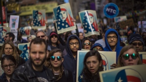 People carry posters during a rally in support of Muslim Americans and protest of President Donald Trump's immigration policies in Times Square, New York on Sunday, Feb. 19, 2017. (AP / Andres Kudacki)