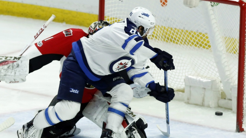 Winnipeg Jets' Mathieu Perreault slides the puck past Ottawa Senators goaltender Mike Condon during first period NHL hockey action in Ottawa on Sunday, Feb. 19, 2017. (Fred Chartrand / THE CANADIAN PRESS)
