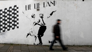 A new piece of art by street artist Bambi in London, on Feb. 16, 2017: Lie Lie Land, features a dancing British Prime Minister Theresa May and U.S. President Donald Trump. (Kirsty Wigglesworth / AP)