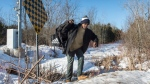 A refugee claimant from Mauritania crosses the border into Canada from the United States Monday, February 20, 2017 near Hemmingford, Que. THE CANADIAN PRESS/Paul Chiasson