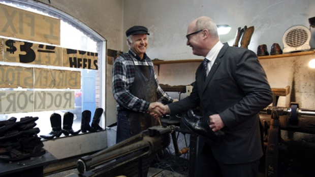 Finance Minister Michael de Jong shakes hands with Olde Towne Shoe Repair owner Mike Waterman after picking up his newly-soled shoes in advance of the provincial budget in Victoria, B.C., on Monday, February 20, 2017. THE CANADIAN PRESS/Chad Hipolito