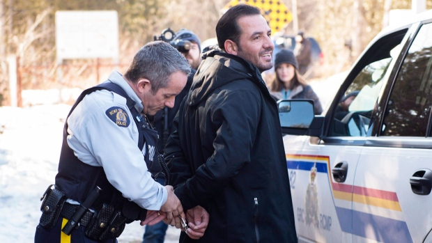 A refugee claimant from Syria is arrested after crossing the border into Canada from the United States Monday, February 20, 2017 near Hemmingford, Que. A growing number of people have been walking across the border into Canada to claim refugee status. THE CANADIAN PRESS/Paul Chiasson
