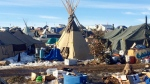 In this Thursday, Feb. 16, 2017, photo, debris is piled on the ground awaiting pickup by cleanup crews at the Dakota Access oil pipeline protest camp in southern North Dakota near Cannon Ball. (AP Photo/Blake Nicholson)