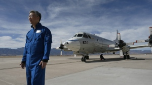 In this Feb. 17, 2017, photo, Ed Kim, a NASA researcher and lead scientist for a NASA-led experiment called SnowEx, stands near a Navy P-3 Orion aircraft used for SnowEx, at Peterson Air Force Base in Colorado Springs, Colo. (AP / Brennan Linsley)
