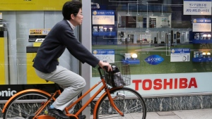 A cyclist passes by a display of Toshiba products on a street in Tokyo, on April 16, 2016. (Koji Sasahara / AP)