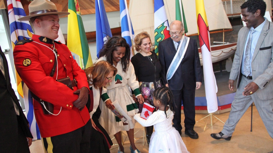 Three-year-old Simboo runs into the arms of her mother, Jelele Etefa, as they pose for a group photo following a Canadian citizenship ceremony at the Maritime Museum of the Atlantic in Halifax, Monday February 20, 2017. Thirty-four new Canadians received their citizenship, held during the province's Heritage Day holiday. (THE CANADIAN PRESS/Str)