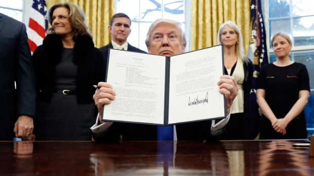 U.S. President Donald Trump holds up a signed Presidential Memorandum to 'develop a comprehensive plan to defeat ISIS,' on Jan. 28, 2017. (Alex Brandon / AP)