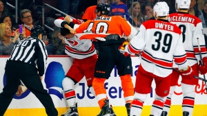 Linesman Scott Cherrey, left, and Carolina Hurricanes' Patrick Dwyer and Jay DeClement, right, watch Philadelphia Flyers' Vinny Lecavalier and Hurricanes' Keegan Lowe fight during the second period of an NHL hockey game, Thursday, April 9, 2015, in Philadelphia. The Hurricanes won 3-1. (AP Photo/Tom Mihalek)