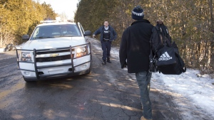 A refugee claimant from Mauritania is greeted by an RCMP officer then arrested after crossing the border into Canada from the United States near Hemmingford, Que. on Monday, Feb. 20, 2017. (Paul Chiasson / THE CANADIAN PRESS)