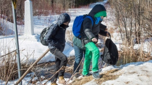A family of asylum claimants cross the border into Canada from the United States, Monday, February 20, 2017 near Hemmingford, Que. A growing number of people have been walking across the border into Canada to claim refugee status. (Paul Chiasson/The Canadian Press)