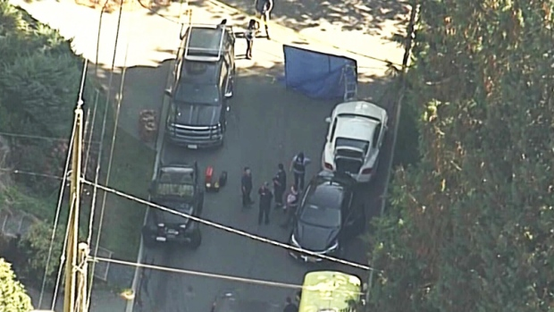 Police surround a vehicle parked on a quiet North Vancouver street while investigating a deadly kidnapping on Sept. 29, 2015. (CTV/Chopper 9)