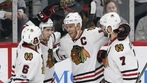 Chicago Blackhawks' Jonathan Toews, second from right, is congratulated on his second goal of the NHL hockey game off Minnesota Wild goalie Devan Dubnyk during the third period of an NHL hockey game, Tuesday, Feb. 21, 2017, in St. Paul, Minn. (AP / Jim Mone)