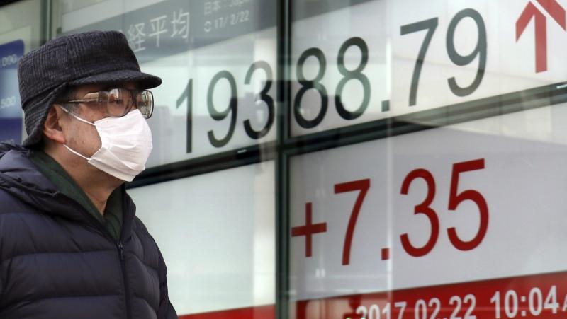 A man walks past an electronic stock indicator of a securities firm in Tokyo, Wednesday, Feb. 22, 2017. (AP / Shizuo Kambayashi)