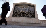 In this March 26, 2011, file photo people walk past the memorial to Union Col. Robert Gould Shaw and the 54th Massachusetts Volunteer Infantry Regiment, near the Statehouse in Boston. (AP Photo/Michael Dwyer)