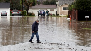 A man walks on a flooded street in Salinas, Calif., on Feb. 20, 2017. (Nic Coury/Monterey County Weekly via AP)