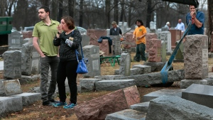 Sally Amon and her son Max Amon of Olivette, Mo., react as they saw toppled gravestone of her grandmother Anna Ida Hutkin at Chesed Shel Emeth Cemetery in University City, on Feb. 21, 2017. (Robert Cohen/St. Louis Post-Dispatch via AP)