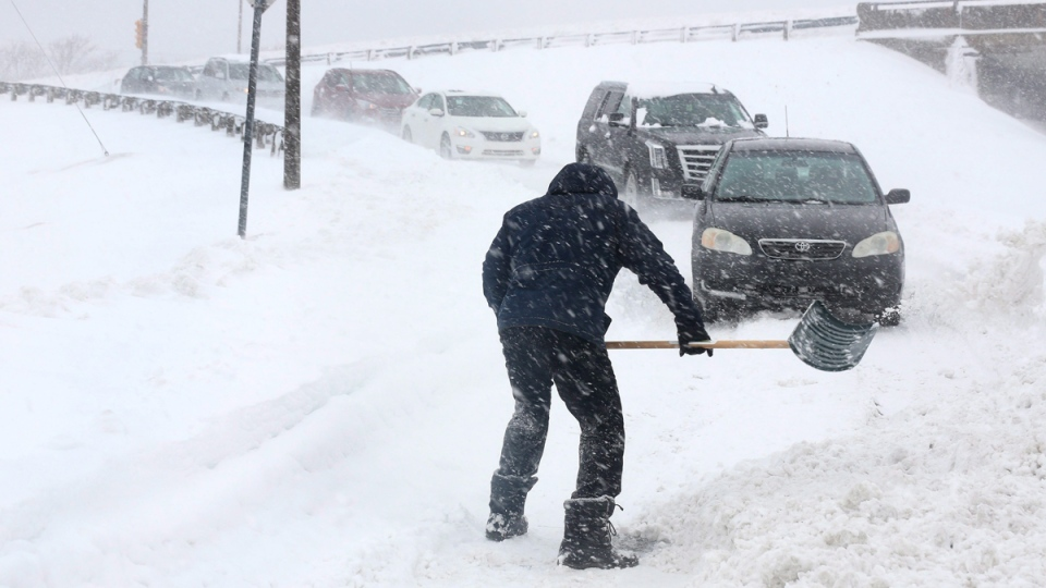 Jide Oduekun has to shovel his way off the exit to Kenmount Road from the Prince Philip Parkway in St. John's N.L. on February 15, 2017. (Paul Daly / THE CANADIAN PRESS)