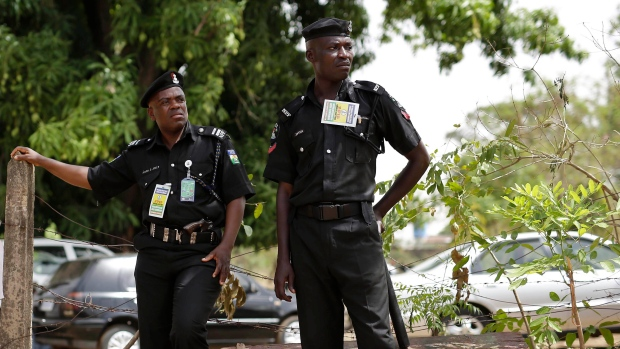 FILE -- Nigerian police officers keep watch as people queue to vote in Kaduna, Nigeria, on Saturday, March 28, 2015. (AP Photo/Jerome Delay)