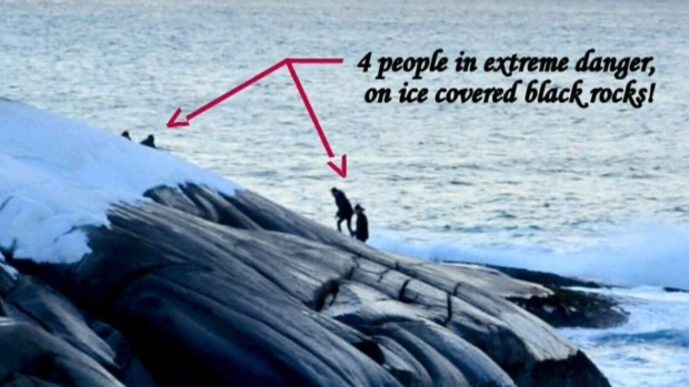 Photographer Warren Hoeg posted this picture on Facebook, showing four people stuck on the black rocks at Peggys Cove Monday night.
