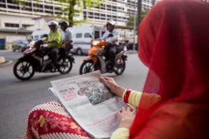 A Malaysian journalist reads a local newspaper reporting the North Korean's death in front of the National Forensic Institute at Kuala Lumpur Hospital in Kuala Lumpur, Malaysia, Thursday, Feb. 23, 2017. (AP / Alexandra Radu)