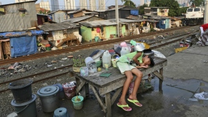A young girl takes a break on a table at a slum near the main business district in Jakarta, Indonesia on July 3, 2014. (AP / Tatan Syuflana)