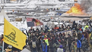 A fire set by protesters burns in the background as opponents of the Dakota Access pipeline leave their main protest camp near Cannon Ball, N.D. on Wednesday, Feb. 22, 2017. (Tom Stromme / The Bismarck Tribune)