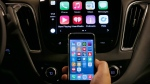 An iPhone is connected to a 2016 Chevrolet Malibu equipped with Apple CarPlay apps, displayed on the car's MyLink screen, top, during a demonstration in Detroit on May 26, 2015. (AP Photo/Paul Sancya)