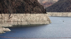 "In this April 16, 2013 file photo, a ""bathtub ring"" marks the high water mark as a recreational boat approaches Hoover Dam along Black Canyon on Lake Mead, the largest Colorado River reservoir, near Boulder City, Nev. (AP Photo/Julie Jacobson, File)"