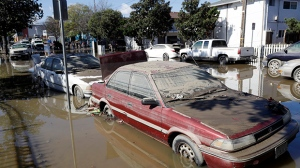 Cars are partially submerged and covered in mud from receding floodwaters Thursday, Feb. 23, 2017, in San Jose, Calif. (AP Photo/Marcio Jose Sanchez)