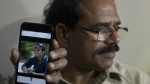 A man shows a picture of Alok Madasani, an engineer who was injured in the shooting Wednesday night in a crowded suburban Kansas City bar, on a mobile phone as Madasani's father Jaganmohan Reddy talks to the media at his residence in Hyderabad, India on Friday, Feb. 24, 2017. (AP / Mahesh Kumar A.)