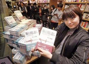 A woman poses with books written by Haruki Murakami, at a book store in Tokyo shortly after midnight, Friday, Feb. 24, 2017. (Kazuhiko Yamashita/Kyodo News via AP)