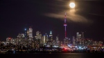 The moon rises behind the skyline in Toronto, Friday January 13, 2017. (Mark Blinch/The Canadian Press)