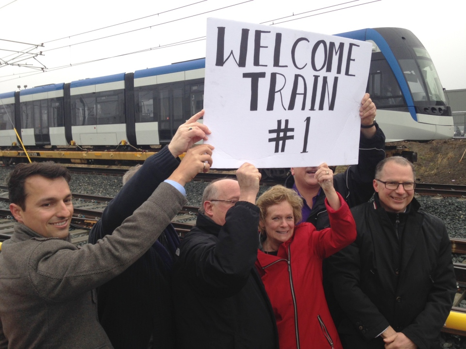 Officials from the Region of Waterloo and Bombardier hold up a sign welcoming the first Ion light rail vehicle to Waterloo on Friday, Feb. 24, 2017. (Marc Venema / CTV Kitchener)