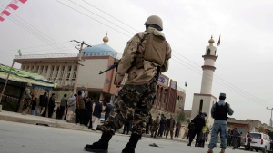 FILE - In this Monday, Nov. 21, 2016, file photo, Afghan security forces and and civilians walk around the Shiite Baqir-ul Ulom mosque after a suicide attack inside it, in Kabul, Afghanistan. (AP Photos/Massoud Hossaini, File)