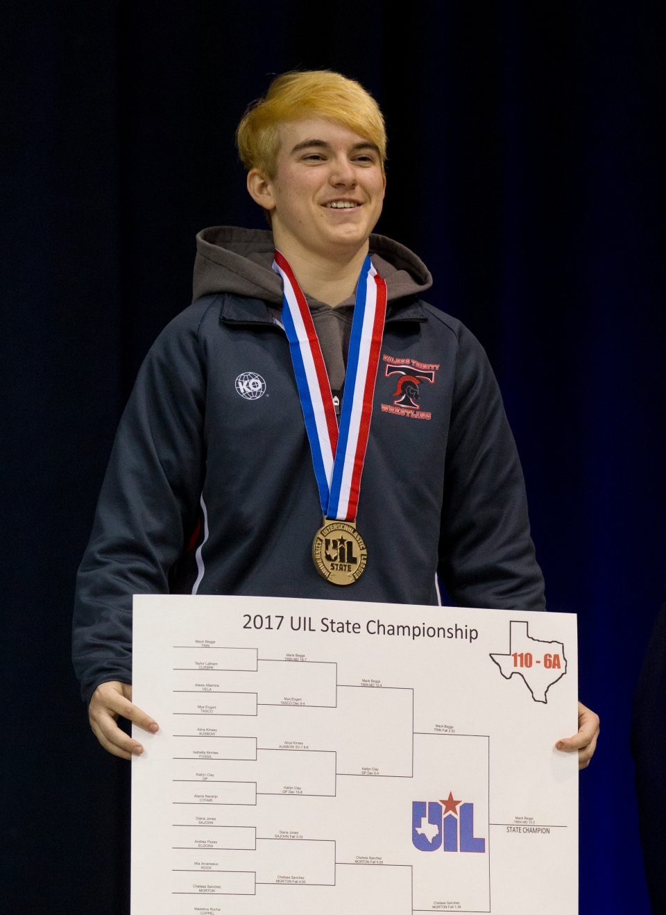 Euless Trinity's Mack Beggs holds a poster with the bracket, after defeating Morton Ranch's Chelsea Sanchez in the girls' Class 6A final at 110 pounds in the state wrestling championships Saturday, Feb. 25, 2017, in Cypress, Texas. Beggs was born female and is transitioning to male but wrestled in the girls division. (Jason Fochtman / Houston Chronicle via AP)