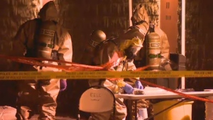 Police in hazardous material suits at the site of a suspected drug lab on Saturday night.