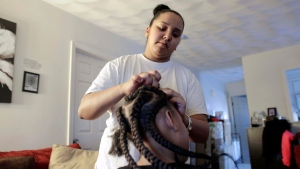 In this Sunday, Feb. 19, 2017 photo Jocelyn DoCouto, top, adds braid extensions for seven-year-old Zanyrah Parrott, of Pawtucket, R.I., in DoCouto's home, in Pawtucket. (AP Photo/Steven Senne)