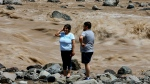 A couple looks at the overflowing Maipo River in San Alfonso, Santiago, Chile, Sunday, Feb. 26, 2017. (AP Photo/Esteban Felix)
