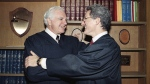 FILE - In this Friday, Oct. 13, 1989, file photo, retired Judge Joseph A. Wapner of TV's 'The People's Court' congratulates his son, Judge Frederick N. Wapner, right, as he was enrobed as a Municipal Court judge in Los Angeles. (AP Photo/Nick Ut, File)
