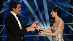 """Sofia Boutella, right, presents Sylvain Bellemare with the award for best sound editing for """"Arrival"""" at the Oscars on Sunday, Feb. 26, 2017, at the Dolby Theatre in Los Angeles. (Photo by Chris Pizzello/Invision/AP)"""