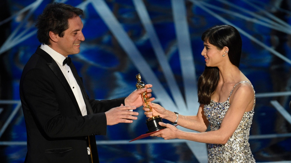 "Sofia Boutella, right, presents Sylvain Bellemare with the award for best sound editing for ""Arrival"" at the Oscars on Sunday, Feb. 26, 2017, at the Dolby Theatre in Los Angeles. (Photo by Chris Pizzello/Invision/AP)"