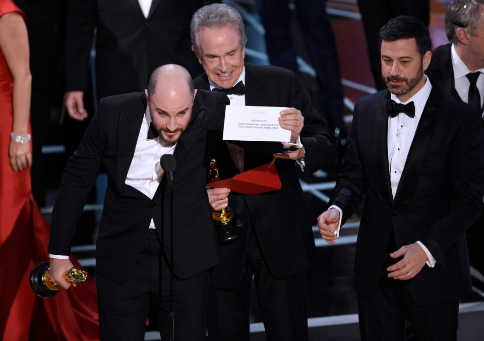 """Jordan Horowitz, producer of """"La La Land,"""" shows the envelope revealing """"Moonlight"""" as the true winner of best picture at the Oscars on Sunday, Feb. 26, 2017, at the Dolby Theatre in Los Angeles. Presenter Warren Beatty and host Jimmy Kimmel look on from right. (Photo by Chris Pizzello/Invision/AP)"""